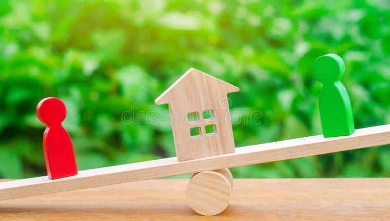 Figuras de madera en las escalas clarificación de la propiedad de la casa, propiedades inmobiliarias rivales en negocio competenc fotografía de archivo libre de regalías