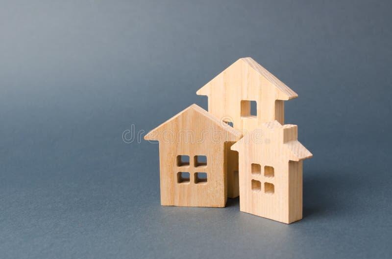 3 figuras de madera de las casas Hogar respetuoso del medio ambiente y respetuoso del medio ambiente Vivienda en los suburbios Te fotos de archivo libres de regalías