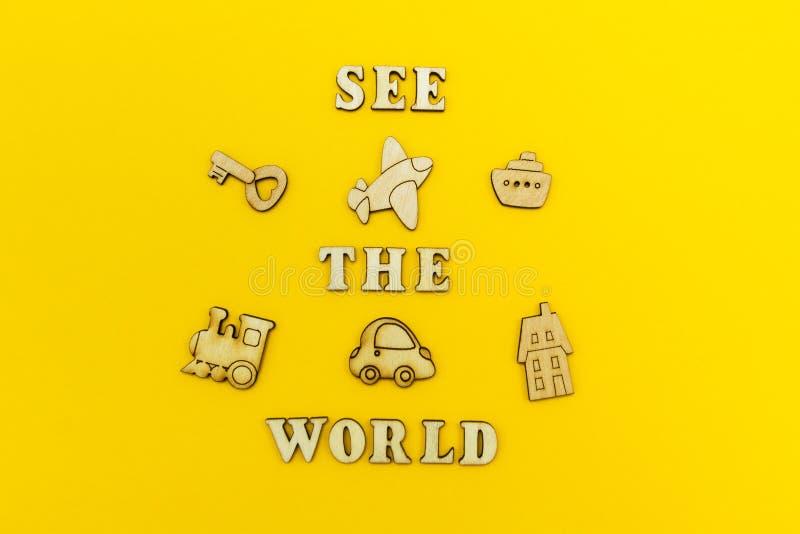 Figuras de madera de un aeroplano, un tren, una nave, un coche La inscripción 'considera el mundo 'en un fondo amarillo foto de archivo