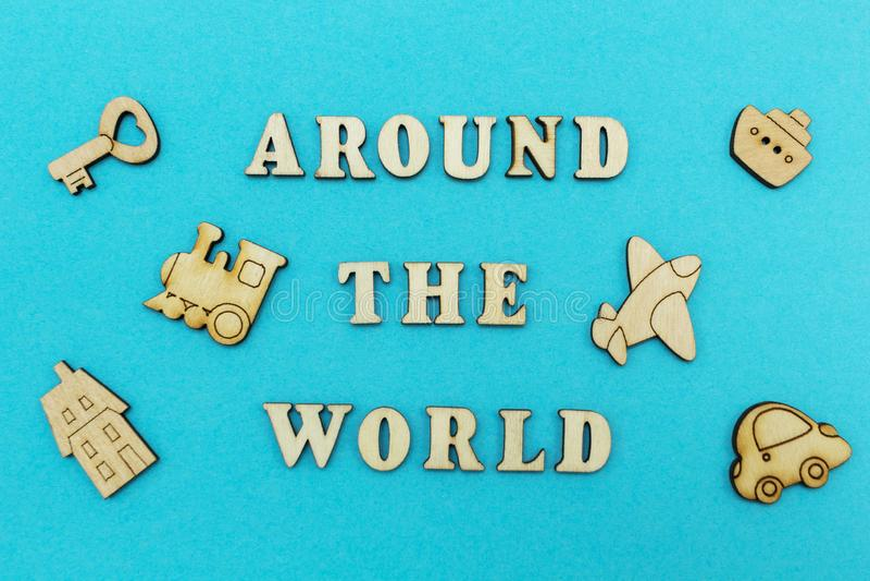 Figuras de madera de un aeroplano, un tren, una nave, un coche La inscripción 'en todo el mundo 'en un fondo azul imágenes de archivo libres de regalías