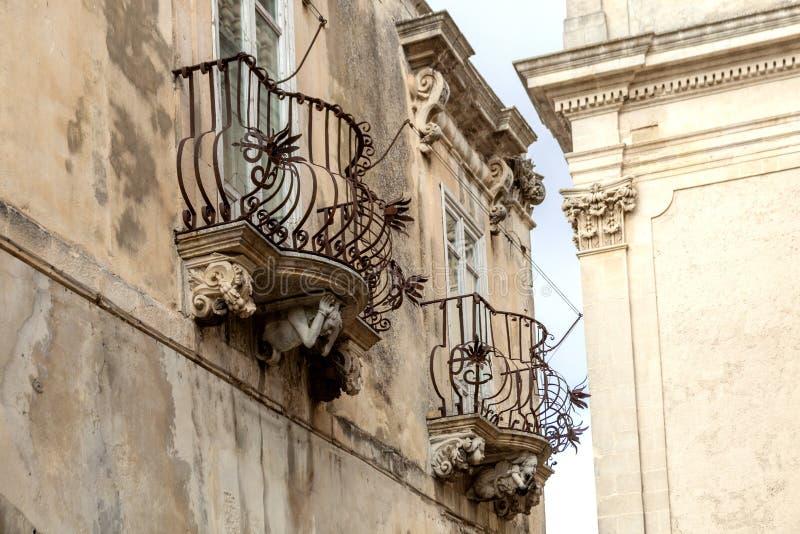 Figuras de pedra antropomórficas sob o balcão do palácio de Rocca do La Ragusa Ibla Sicília Itália fotos de stock royalty free