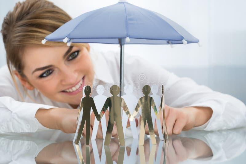 Figuras de protección del recorte de la empresaria con el paraguas foto de archivo libre de regalías