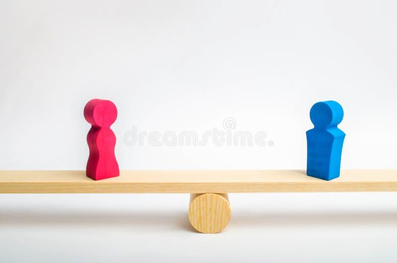 Figuras de um homem e de uma mulher nas escalas conceito da desigualdade: o homem e as mulheres em um peso equilibram, diferença  foto de stock royalty free