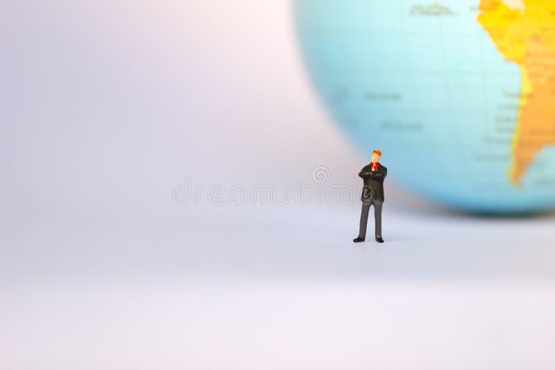 Figuras do homem de neg?cios pequeno que est?o no ponto de viragem no fundo da terra imagens de stock royalty free