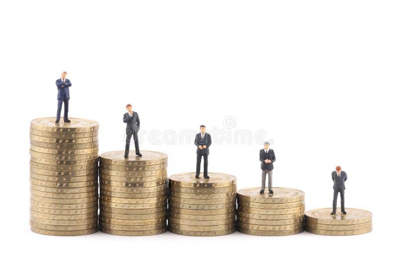 Figuras do negócio em pilhas de moedas imagens de stock