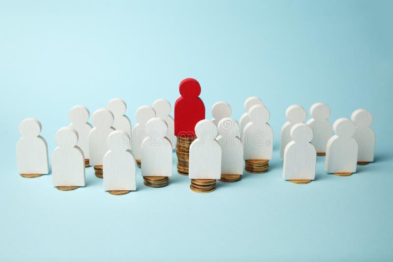 Figuras dos povos em pilhas de moedas Níveis diferentes do salário do pessoa, crescimento da pensão fotografia de stock