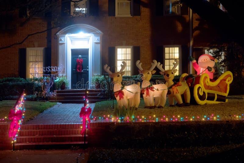 Figuras infláveis: Santa Claus em um trenó com os cervos perto do h imagem de stock royalty free