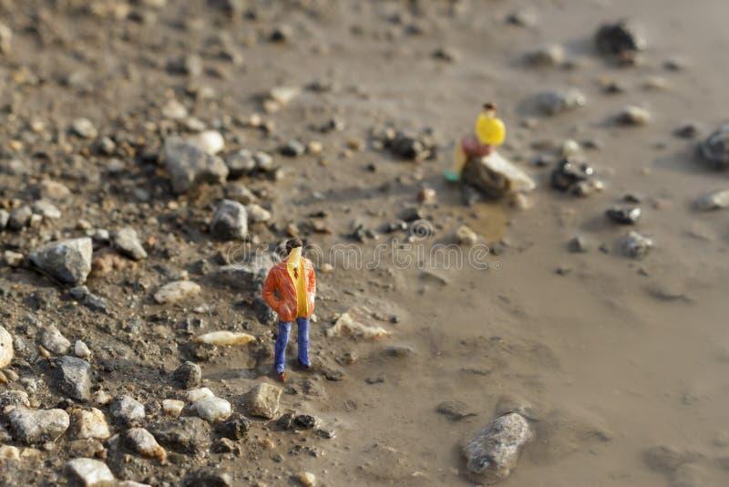 Figuras miniatura en la tierra fotos de archivo