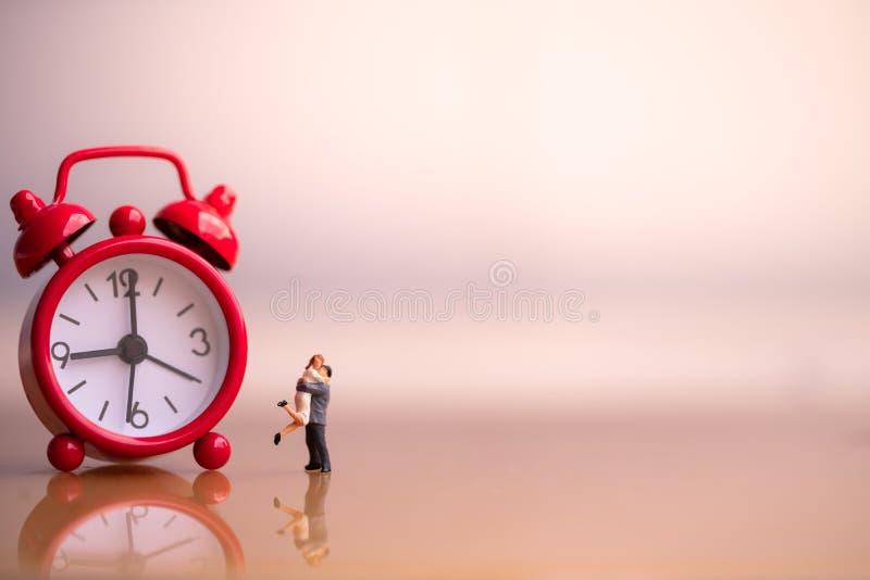 Figuras pequenas dos pares no amor e no despertador vermelho foto de stock royalty free