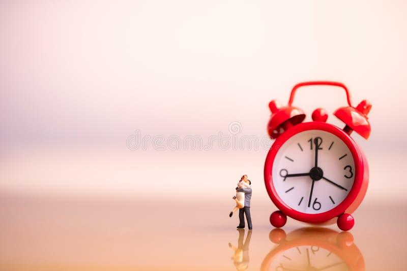 Figuras pequenas dos pares no amor e no despertador vermelho imagem de stock