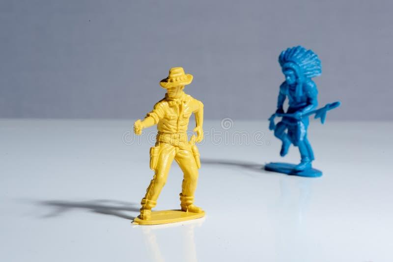 Figuras pl?sticas del juguete del indio azul y del vaquero amarillo imagen de archivo libre de regalías