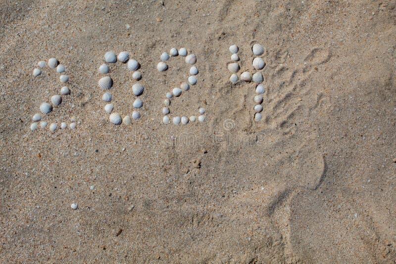 """Figure """"2024 """"est présentée sur le sable avec des coquilles photographie stock"""