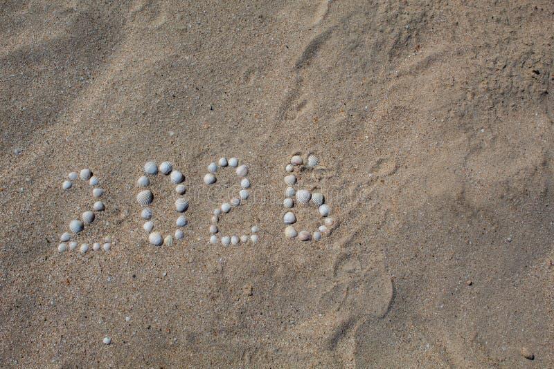"""Figure """"2026 """"est présentée sur le sable avec des coquilles photos stock"""