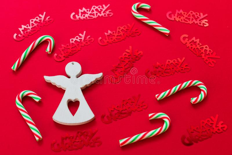The figure of a white angel Christmas candy and red shiny lettering with Christmas on a red background. royalty free stock photography