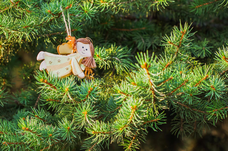 Figure of an angel on green spruce Christmas tree decoration stock image