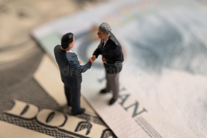 Figure businessman standing on US dollar and YUAN banknote, are holding hands to success in trade agreements. Concept of trading w. Ar royalty free stock images