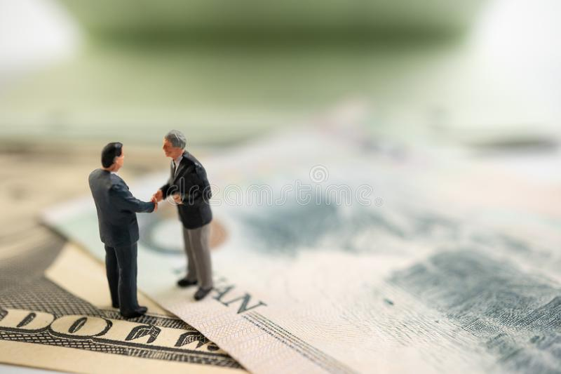 Figure businessman standing on US dollar and YUAN banknote, are holding hands to success in trade agreements. Concept of trading w. Ar royalty free stock photography