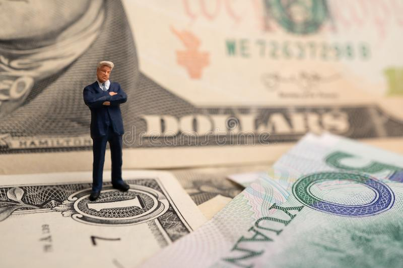 Figure businessman standing on US dollar and YUAN banknote, are holding hands to success in trade agreements. Concept of trading w. Ar stock photos