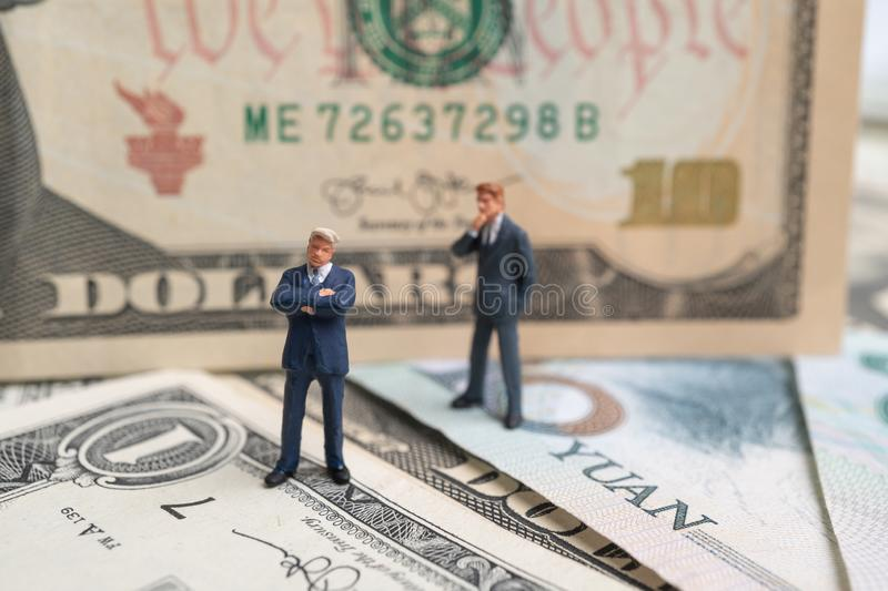 Figure businessman standing on US dollar and YUAN banknote and thinking. Concept of trading war royalty free stock photo