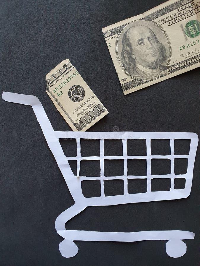 figure d'un chariot sur papier blanc et billet américain cassé de 100 dollars photos stock