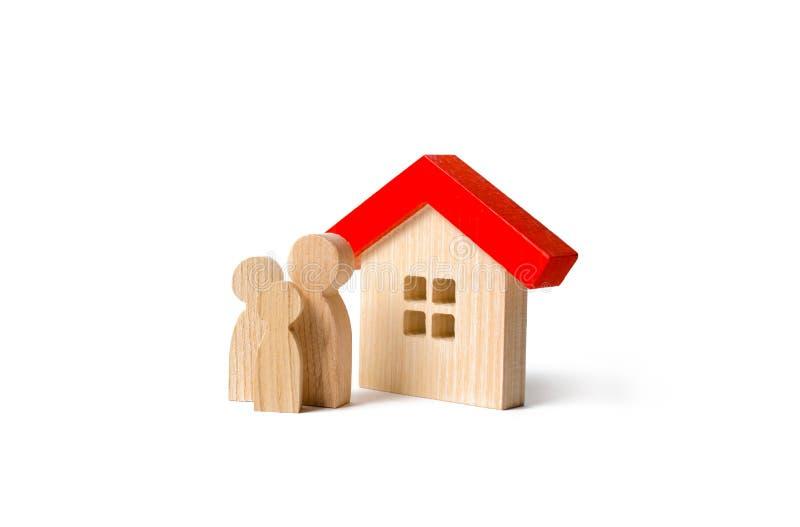 Figure della famiglia e della casa su un fondo isolato bene immobile, la vostra propria casa Acquisto o vendere Alloggiamento acq immagini stock
