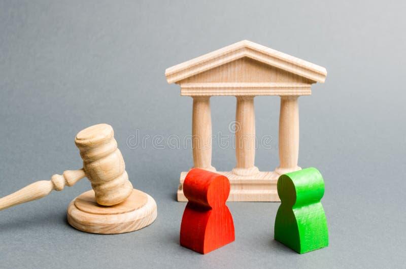 Figure di legno della gente che sta vicino al martelletto del giudice controversia Rivali di affari Legge e giustizia di conflitt fotografia stock libera da diritti