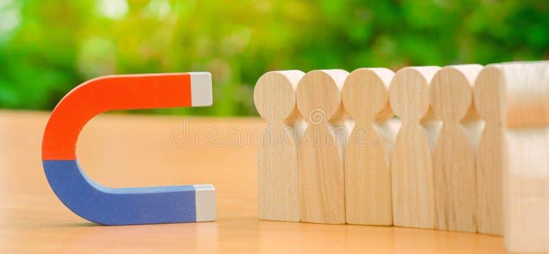 Figure di legno della gente e di un magnete Concetto della gestione del gruppo Risorse umane promuova Scelta del capo nuovo ed as fotografie stock libere da diritti