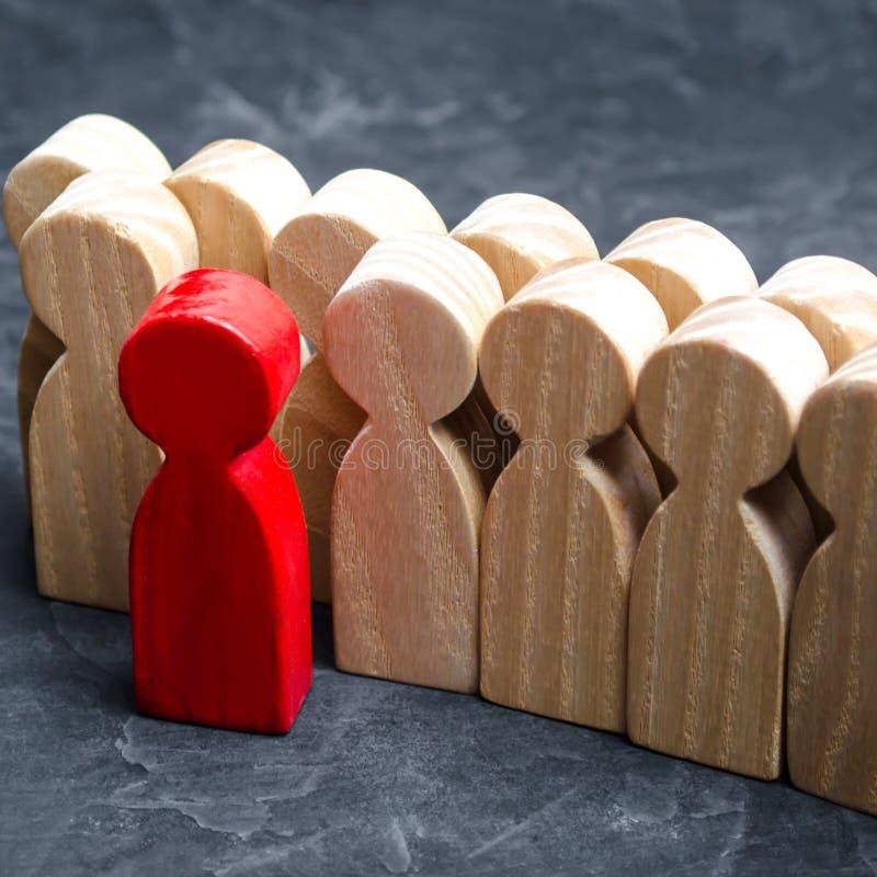 Figure di legno della gente L'uomo rosso esce con un gruppo dei lavoratori Il concetto di scelta del capo nuovo Scelta della pers immagine stock