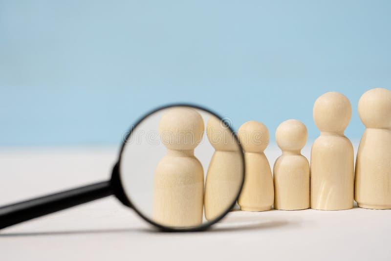 figure di legno di persone con lente di ingrandimento su sfondo blu immagini stock libere da diritti