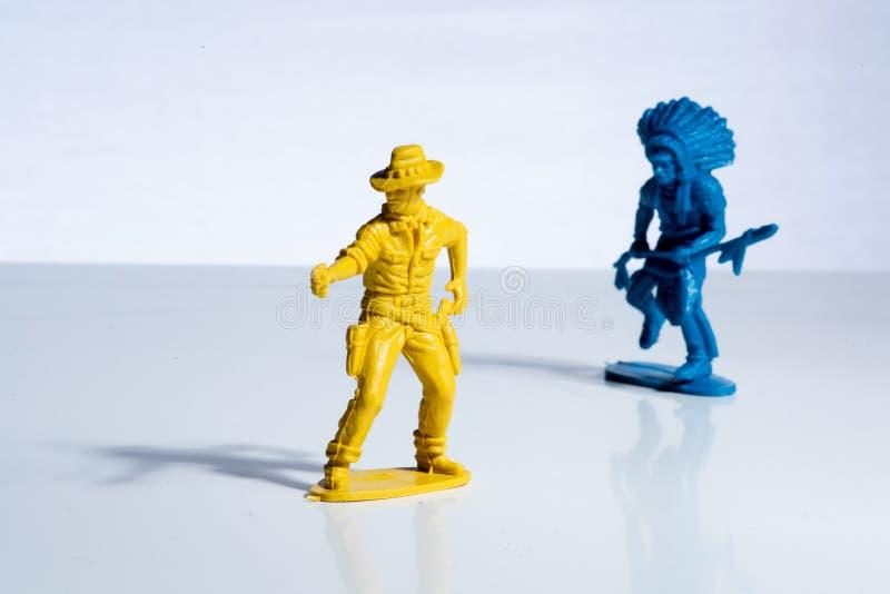 Figure di plastica del giocattolo del cowboy giallo e dell'indiano blu fotografia stock