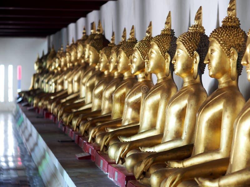 Figure di seduta statue di Buddha di meditazione dorata dentro il corridoio fotografia stock