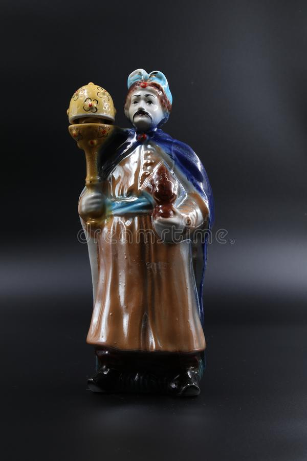 Figure of the dvolny grandee with a mace in a blue raincoat and with moustaches. Subject shooting against a dark background royalty free stock photo