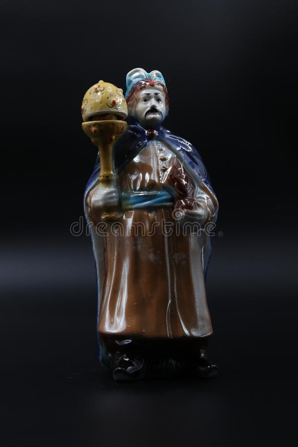 Figure of the dvolny grandee with a mace in a blue raincoat and with moustaches. Subject shooting against a dark background stock photography