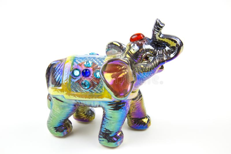 The figure of an elephant made of ceramics is decorated with colored mother-of-pearl paints turquoise purple silver Inserts of col. The figure of an elephant stock photos