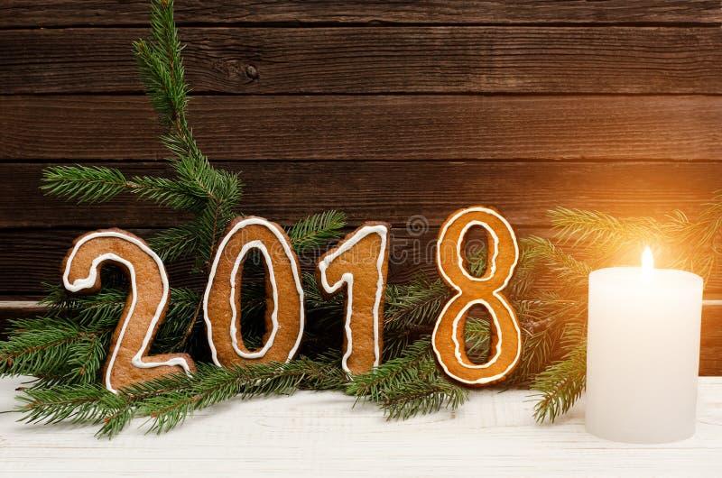 Figure em 2018 do pão-de-espécie no fundo de ramos spruce e de paredes de madeira, vela branca fotos de stock royalty free