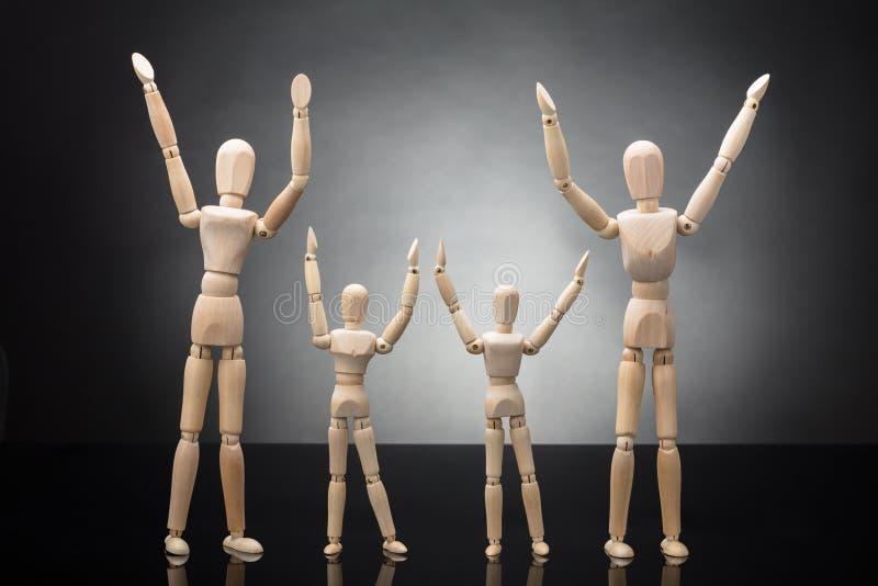 Figure en bois parents et enfants factices soulevant leurs bras images libres de droits