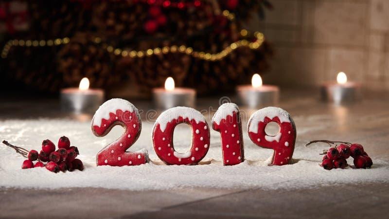 Figure 2019 fatte dai biscotti dello zenzero e dalle bacche di sorbo Tavola scura coperta di neve Disposizione di Natale sulla ta immagine stock
