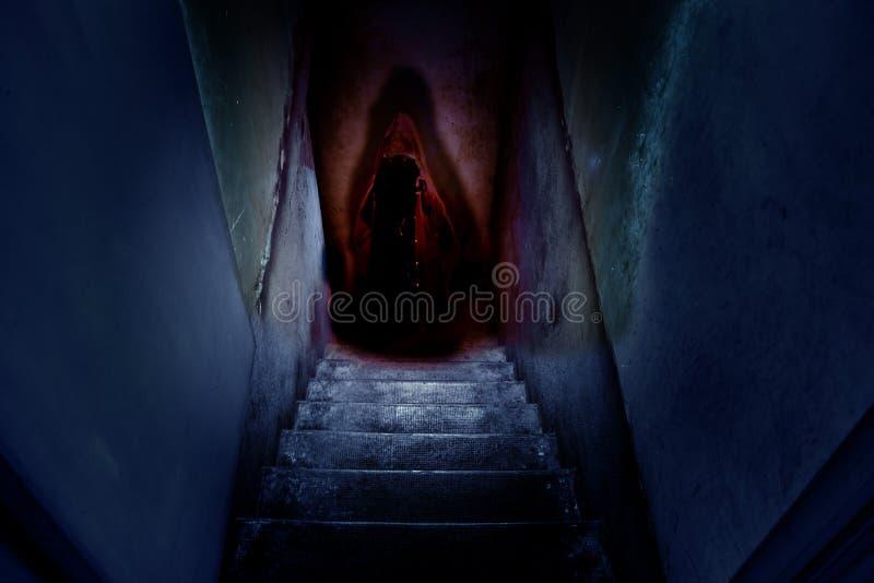 Figure foncée dans un cap rouge avec un capot sur les vieux escaliers concrets dans la descente au sous-sol photos libres de droits