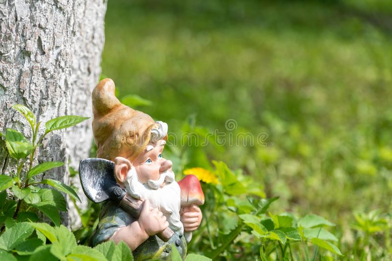 The figure of a garden gnome with a shovel at a tree in the green grass. Close-up. Copy space royalty free stock photos