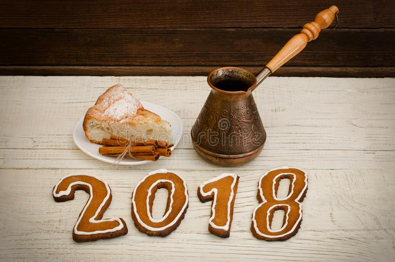 Figure in 2018 of gingerbread, pots and apple pie on a wooden table stock photos