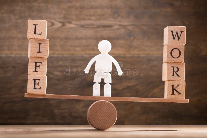 Figure humaine se tenant entre le travail et les blocs en bois de la vie photographie stock