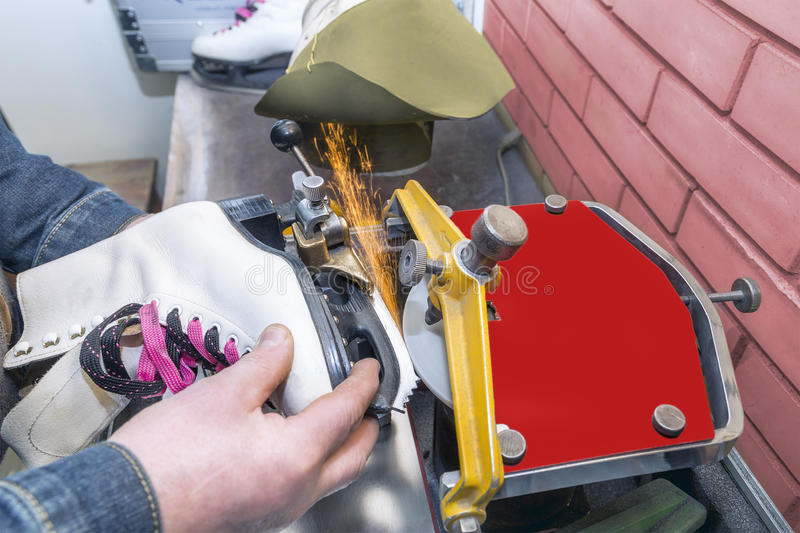Figure ice skate getting sharpened stock photography