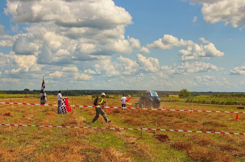 Figure la concurrence de pilotage au champ Vieux tracteur bleu sur la voie Festival Brusviana de baie image libre de droits