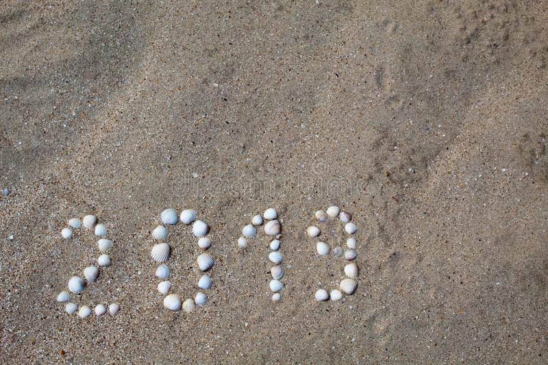 The figure `2019` is laid out on sand with shells. stock images