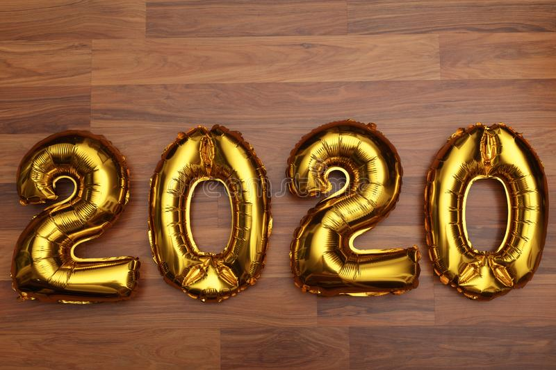 Figure 2020 made of balloons on wooden background.  royalty free stock photo