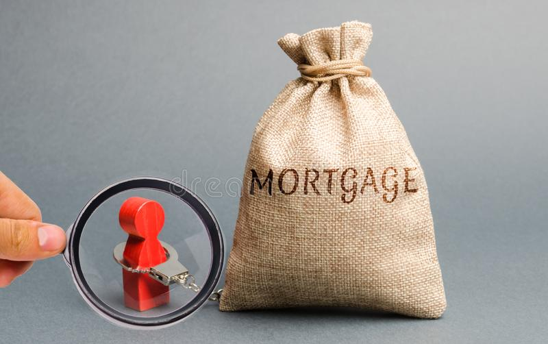 The figure of a man is handcuffed to a money bag with the word Mortgage. Impossibility of paying interest rates on mortgages and stock photos