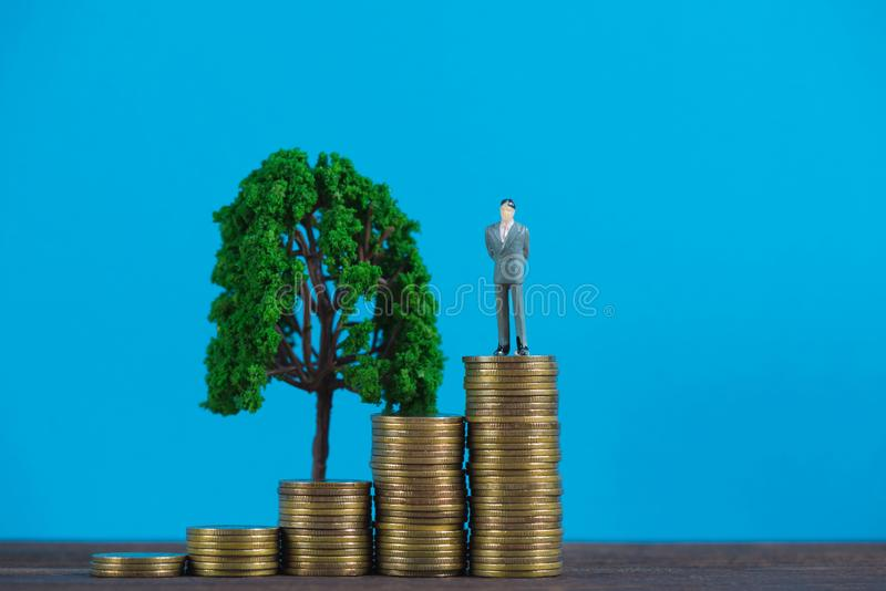 Figure miniature businessman or small people investor standing on coin stack with little tree decoration, for money and financial royalty free stock image