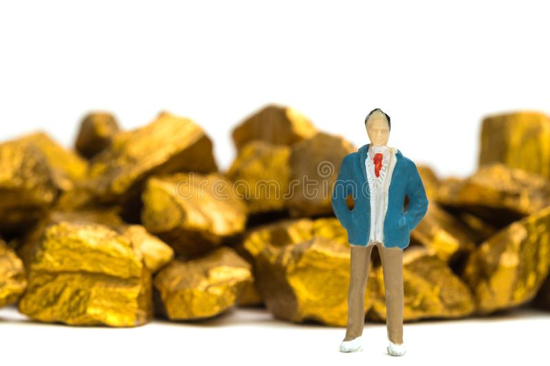 Figure miniature businessman or small people with pile of gold n. Uggets or gold ore on white background, precious stone or lump of golden stone, financial and stock photography
