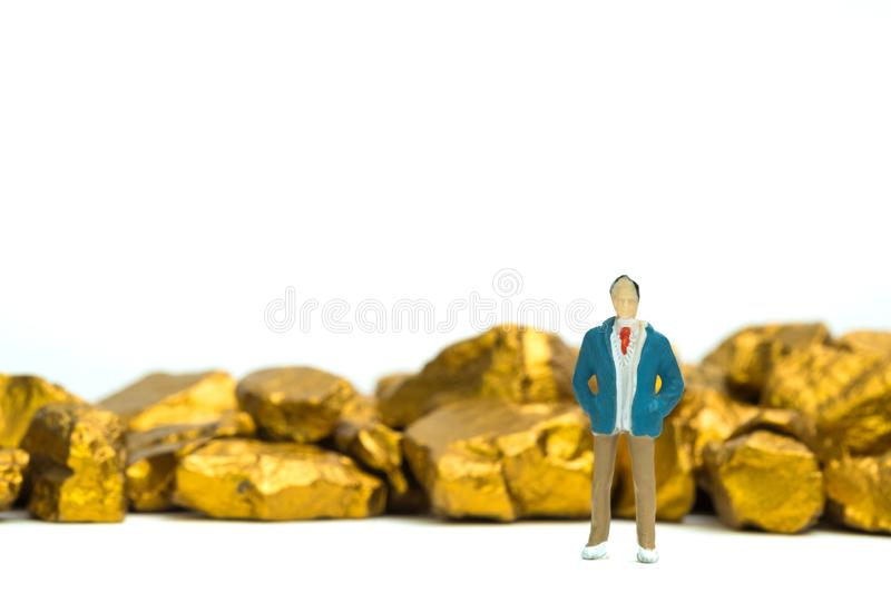 Figure miniature businessman or small people with pile of gold n. Uggets or gold ore on white background, precious stone or lump of golden stone, financial and royalty free stock photo