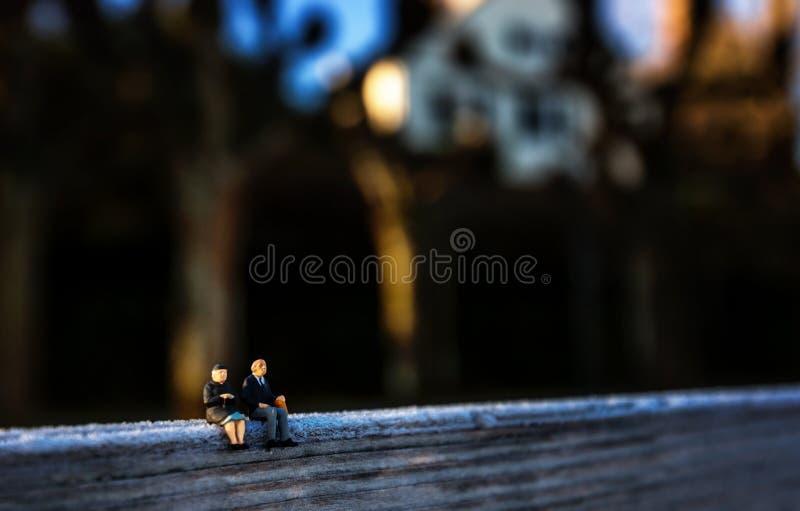 Figure miniature du grand-papa et de la grand-maman s'asseyant sur un banc en hiver images libres de droits